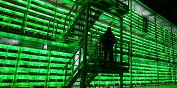 An armed guard patrols in front of illuminated mining rigs mounted inside racks at the BitRiver Rus LLC cryptocurrency mining farm in Bratsk, Russia, on Friday, Nov. 8, 2019. Bitriver, the largest data center in the former Soviet Union, was opened just a year ago, but has already won clients from all over the world, including the U.S., Japan and China. Most of them mine bitcoins. Photographer: Andrey Rudakov/Bloomberg via Getty Images
